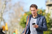 Young urban businessman professional on smartphone walking in street using app texting sms message o