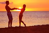 Romantic couple fun on beach sunset during travel. Happy woman and man holding hands playful on hone