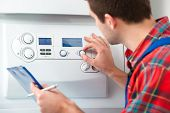pic of gas-pipes  - Technician servicing the gas boiler for hot water and heating