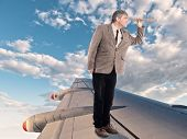 businessman with spyglass standing on an airplane wing