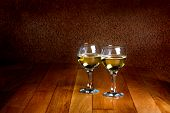 Two Wineglasses Of White Wine On Wooden Old Counter Top
