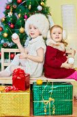 Two little girls sit on wooden bench back to back with decorated artificial new year tree at backgro