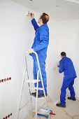 Back of two men in blue, pasting paint fiberglass and painting wall in new apartment