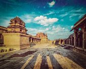 Vintage retro hipster style travel image of Krishna temple on sunset with grunge texture overlaid. Royal Center, Hampi, Karnataka, India