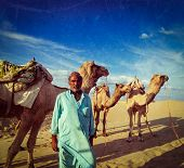 Vintage retro hipster style travel image of Rajasthan travel background Indian man cameleer (camel d