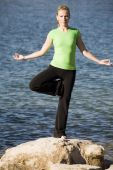 Yoga Woman Standing On One Leg By Water