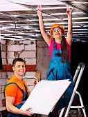 People in builder uniform installing suspended ceiling