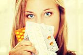 image of contraception  - Young beautiful ill woman with pills - JPG