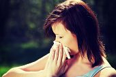 Young woman with allergy during sunny day is wiping her nose. Girl in summer dress with runny nose,