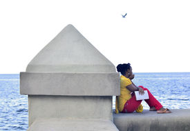 pic of malecon  - A beautiful black girl sitting on Malecon in Havana in front of the sea dreaming and holding her notes in her hand