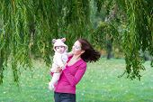Mother And Daughter Standing Under A Colorful Willow Tree On A Windy Day