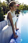 picture of beside  - fashion outdoor photo of beautiful bride with blond hair in elegant wedding dress posing beside a swimming pool - JPG
