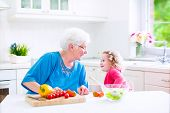 picture of love making  - Beautiful senior lady happy loving grandmother making healthy salad for lunch with her granddaughter cute curly little girl in a white sunny kitchen with window cutting pepper and tomato - JPG
