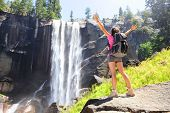 Hiking woman freedom in Yosemite national park by waterfall. Cheering happy hiker enjoying view of beautiful Vernal Fall. Young girl on hike in beautiful summer nature landscape, California, USA.