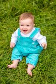 ?ute Little Baby Boy Siitting On The Grass At A Park