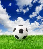 Soccer Ball On Green Grass Over Dramatic Blue Sky