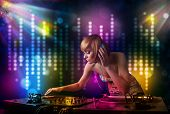 Pretty Dj girl playing songs in a disco with light show