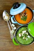 two kinds of cream soup (broccoli and pumpkin) in pot on wooden background