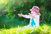 stock photo of flying-insect  - Happy laughing little girl wearing a blue dress and colorful straw hat playing with a flying butterfly having fun in the garden on a sunny summer day - JPG