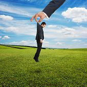 big hand holding small sad businessman in suit over green field and blue sky