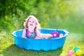 Toddler Girl Playing Wil Balls In The Garden