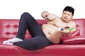 Asian Male Watching Tv And Holding Donuts