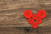 Red Buttons Shaped Heart Over Wooden Background
