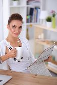 Cute businesswoman holding newspaper sitting at her desk in bright office