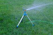 Mobile sprinkler system mounted on tripod working on fresh green grass