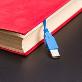 Usb cable sticks out from red book