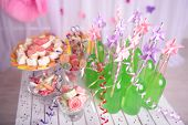 Bottles of drink with straw and sweets on decorative background