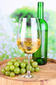 Tasty wine and ripe grape on green nature background