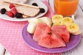 Slices of fruits with crispbreads and glass of juice on table close up