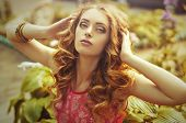 Beautiful young woman with makeup in fashion clothes on nature