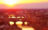 Ancient Italian bridge across Arno river in bright yellow sunset light, Florence, Europe, famous his