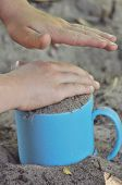 Sand, Mug, Child's Play In The Sand. Hands Of The Child.
