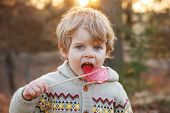 Little Caucasian Toddler Boy Of Two Years Eating Big Candy