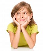 Portrait of a pensive little girl supporting her head with hands, isolated over white