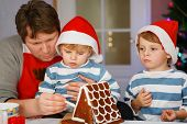 image of father time  - Father and two little sons preparing a gingerbread cookie house at christmas time - JPG