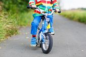 Child In Colorful Raincoat Riding His First Bike