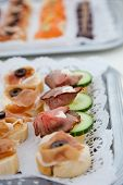 stock photo of buffet catering  - Canapes or appetizers with assorted cold meat displayed on a tray on a buffet table at a wedding reception or catered event  - JPG
