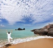 Thailand. Gorgeous beach on the Andaman Sea. Middle-aged woman dressed in white doing yoga
