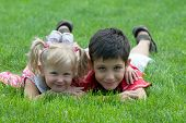 image of brother sister  - a little girl and a boy are lying on the grass in the park - JPG