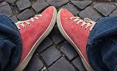 Feet In Red Sneakers And Jeans Outdoors.