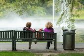 stock photo of dustbin  - Two women lost in their thoughts stare to the fountain in the park sitting on a wooden bench beside a dustbin - JPG