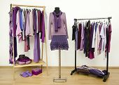 Wardrobe with purple clothes arranged on hangers and an outfit on a mannequin.