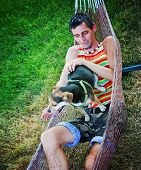 a young man in a hammock cuddling with his chihuahua beagle mix dog