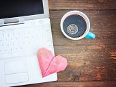 Laptop or notebook with cup of coffee and origami heart on old wooden table