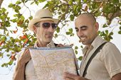 Sightseeing: Middle aged gay couple on vacation search the way with map