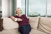 Senior woman with coffee mug sitting on sofa at home